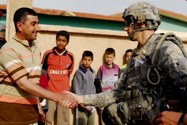 BAGHDAD - The Iraqi headmaster (left) of the local school in Owesat greets Detroit native Lt. Col. Brian Eifler (right), commander, 1st Battalion, 6th Infantry Regiment, during Operation  Al Sakar April 12. The Iraqi Army and 'Iron' Brigade conducted a combined counter insurgency operation in the Owesat area to clear the area of insurgents, weapons and explosives caches. Both forces' goal was to hold and secure the Owesat area and deny insurgents the ability to use the area to launch attacks in the streets of Baghdad.