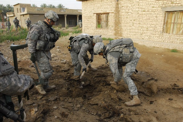 BAGHDAD - Pvt. Johnathon Strain (left), of Olatha, Kan., Pvt Lamont Raynor (center), of Brownsville, N.Y., and Cpl. Kevin Graham, of Oakland, Calif., dig for suspected weapons caches in the Qarghuli Village of the Mahmudiyah Qada during Operation Bein Al-Nahrein April 13. All of the Soldiers serve with Company A, 40th engineers, 2nd Brigade Combat Team, 1st Armored Division, Multi - National Division - Baghdad.