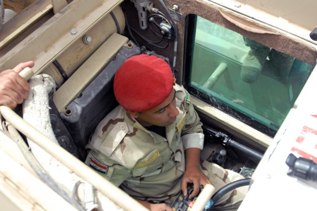 BAGHDAD - An Iraqi engineer student from the 17th Iraqi Army Engineer Regiment sits in the cab of a Husky route clearance vehicle using a control box to maneuver the ferret arm which extends out in front of the vehicle at Joint Security Station Deason April 16.