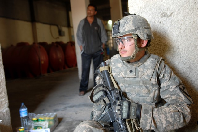 BAGHDAD - Cavalry scout, Spc. James Powell, from Fort Pierce, Fla., assigned to the1st Sqdn., 7th Cav. Regt., 1st BCT, 1st Cav. Div., takes a break inside a water bottling plant during a civil affairs patrol to help raise awareness for a factory owner's council in Boob al-Sham here, April 14. The cavalry scouts provide security and assist the civil affairs' arduous mission to meet most of the factory owners in the neighborhood.