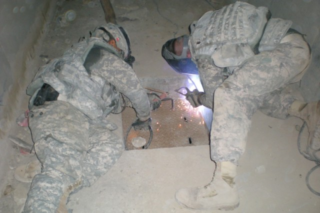 Spc. Eduardo Bonilla, from Jacksonville, N.C., and Spc. Stephen Green, from Pensacola, Fla., both from the 46th Engineer Combat Battalion (Heavy), 225th Engineer Brigade, weld a drainage port shut on a heavily traveled route in western Baghdad.