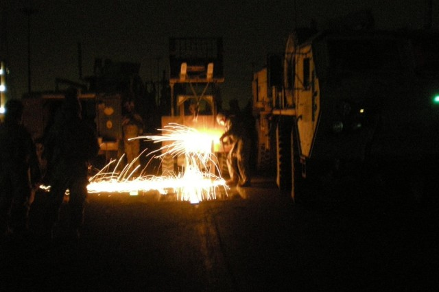 Sparks fly as welders from the 46th Engineer Combat Battalion (Heavy), 225th Engineer Brigade, ensure access to underground tunnels is shut off to terrorists. The engineers were called out to seal access to the tunnels and fix the holes left by a previous bombing. After the site was tampered with, the engineers returned to guarantee the site would be safe for civilian and military traffic.
