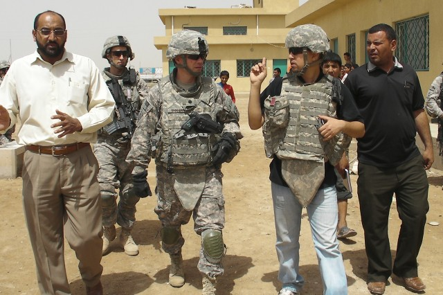 AL-MADAIN, Iraq - Sa'ad Salmin (left), the Al-Madain community sports chairman, walks with Lt. Col. Michael Shinners (center), of Alexandria, Va., during a site assessment mission April 18 in the Al-Madain area of eastern Baghdad. Shinners, who serves as the deputy commander of the 3rd Brigade Combat Team, 82nd Airborne Division, Multi-National Division - Baghdad, surveyed several soccer fields in the region in preparation for an upcoming series of soccer clinics and tournaments that will be organized by FC Unity. Along with the soccer-based programs, the organization will also donate soccer uniforms and equipment to hundreds of aspiring soccer players across Baghdad.