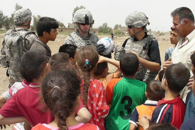 """AL-MADAIN, Iraq - Lt. Col. Michael Shinners (center), of Alexandria, Va., shows a group of children a soccer ball with the name Pfc. Nick Madaras written on it while telling them the meaning behind the ball during a site assessment mission April 18 in an eastern Baghdad neighborhood. Shinners, who serves as the deputy commander of the 3rd Brigade Combat Team, 82nd Airborne Division, Multi-National Division-Baghdad, told them the ball was donated by the """"Kick for Nick"""" organization in honor of the fallen Soldier whose wish was to share his love of soccer with the children of Iraq. Madaras was killed by an improvised explosive device while conducting combat operations Sept. 3, 2006."""