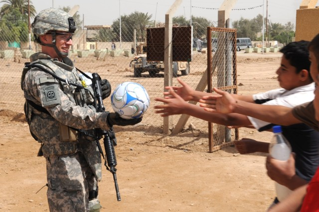 """AL-MADAIN, Iraq - 1st Lt. Benjamin Martin, of Sarasota, Fla., prepares to hand a soccer ball to a charging group of Iraqi children during a site assessment mission April 18 in the Al-Madain area of eastern Baghdad. Martin, who serves as the executive officer for Company B, Brigade Special Troops Battalion, 3rd Brigade Combat Team, 82nd Airborne Division, Multi-National Division-Baghdad, and other paratroopers donated several soccer balls donated by the """"Kick for Nick"""" organization. The organization was founded in honor of Pfc. Nick Madaras whose wish was to collect soccer balls and give them to the children of Iraq. Madaras was killed by an improvised explosive device while conducting combat operations Sept. 3, 2006."""