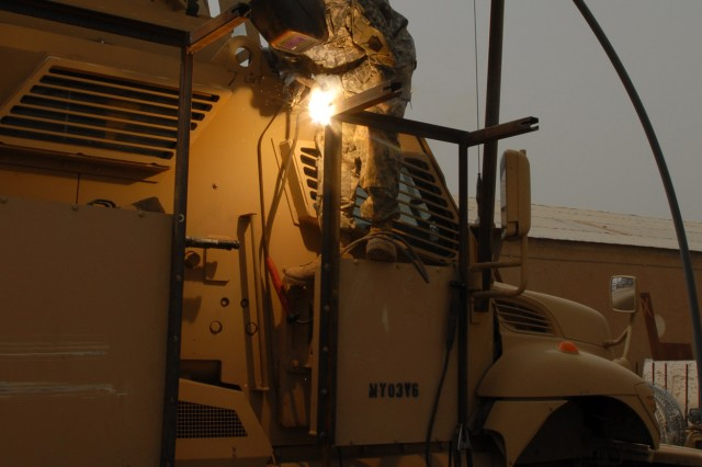 BAGHDAD - Spc. Richard Pfleegor of Jersey Shore, Pa., a Soldier with Company B, 328th Brigade Support Battalion, 56th Stryker Brigade Combat Team, welds outriggers onto a bolt-on metal frame April 16. The frame is the support for a Hesco mesh wire apparatus installed to deflect hand-thrown explosives from Mine Resistant Ambush Protected vehicles.