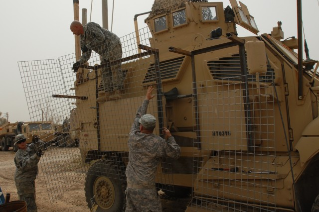 BAGHDAD - Spc. Samantha Schell (left), of Philadelphia, and Sgt. William Funaro of Monroeville, Pa. hand up Hesco wire to Spc. Richard Pfleegor of Jersey Shore, Pa. who positions it on a metal outrigger. The Soldiers of the 328th Brigade Support Battalion, 56th Stryker Brigade Combat Team place the mesh wire apparatus on their Mine Resistant Ambush Protected vehicles to protect them from hand-thrown explosives.