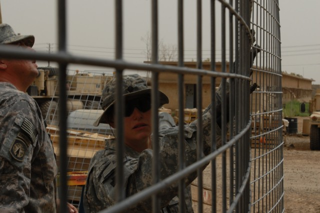BAGHDAD - Spc. Samantha Schell of Philadelphia holds a piece of wire mesh in place as Sgt. William Funaro of Monroeville, Pa. looks on April 16 at Camp Taji. The Soldiers of the 328th Brigade Support Battalion, 56th Stryker Brigade Combat Team place the mesh wire apparatus on Mine Resistant Ambush Protected vehicles to protect them from hand-thrown explosives.
