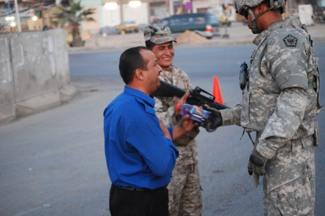 BAGHDAD - While building relations local Iraqi Security Forces, Aurora, Colo. native, Spc. Tyrone Hale, a medic for the 576th Engineer Company, 4th Eng. Battalion, 225th Eng. Brigade, gives drinks to an Iraqi Policeman and an Iraqi Army Soldier March 26.