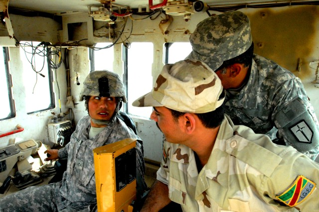 """Pfc. Eric Salinas (left), from Victoria, Texas, a heavy equipment operator with the 277th Engineer Company, 46th Eng. Battalion, 225th Eng. Brigade, explains controls and maneuvers in the cab of a bulldozer to his Iraqi Army counterpart through the use of an interpreter on Victory Base Complex April 16.  Salinas takes pride in providing guidance to IA personnel.  """"It's an honor.  Not many Soldiers get the opportunity to teach the Iraqis how to operate equipment,"""" he said."""