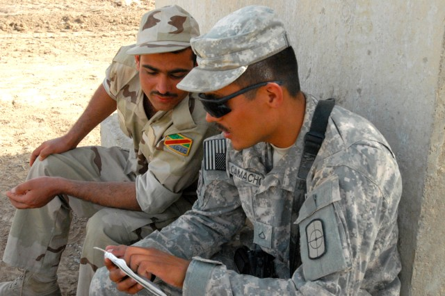 Pfc. Santos Camacho, from Pleasanton, Texas, a heavy equipment operator with the 277th Engineer Company, 46th Eng. Battalion, 225th Eng. Brigade, takes time to practice some Arabic phrases with an Iraqi Army Soldier on Victory Base Complex April 16, while waiting to take turns using heavy equipment.  277th Engineers are leveling ground to expand the runway at Baghdad International Airport and training Iraqi Army Soldiers on the scope of work involved on a general construction site at the same time.