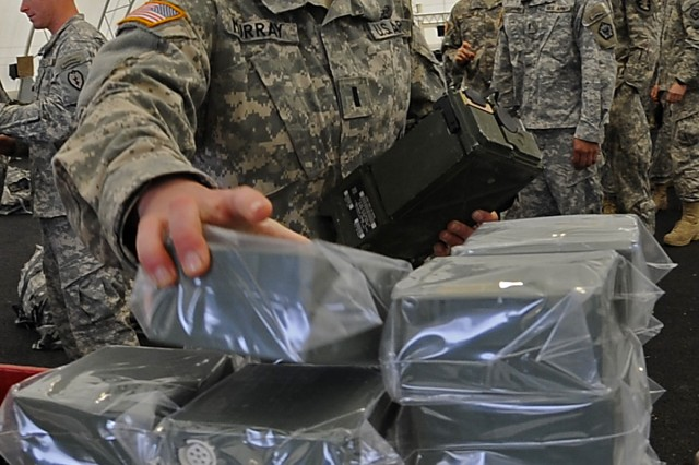 "1st Lt. Christine Murray grabs essential communications gear at an issue point prior to the start of the 2009 ""Best Sapper"" competition at Fort Leonard Wood, Mo. The competition pits the best engineers in the Army against each other during a grueling 52-hour competition."