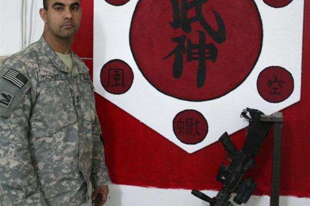 Sgt. 1st Class Robert Tackett, medical platoon sergeant, 1st Battalion, 185th Armor, stands next to the mural he painted on an old card table as a gift to his sensei (teacher), 8th Shodan Ryan Lowe, at Contingency Operating Base Speicher, Iraq, March 29.