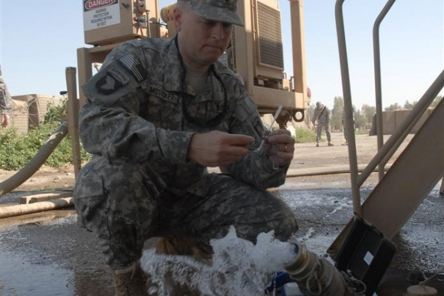 Spc. Gerald McVicker, from Fairmont, W.Va., and the water treatment specialist with the 20th Quartermaster Company, tests the water's chlorine levels after the water purification process at Forward Operating Base Normandy, Iraq. Pure water is then delivered around the various base facilities to include the Iraqi Army Camp Falock, while accommodating more than 1,200 service members and contractors.