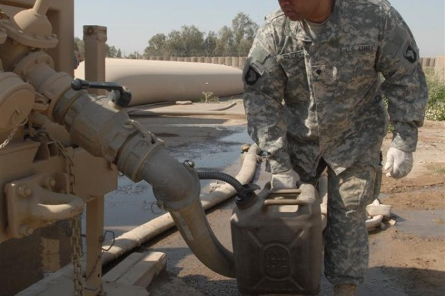 Spc. Kevin C. Fleet, from Miami, Fla., a water purification specialist with the 20th Quartermaster Company, refills a pump with purified water at Forward Operating Base Normandy, Iraq. The purified water is delivered to various facilities around the FOB and to the Iraqi Army camp, Camp Falock