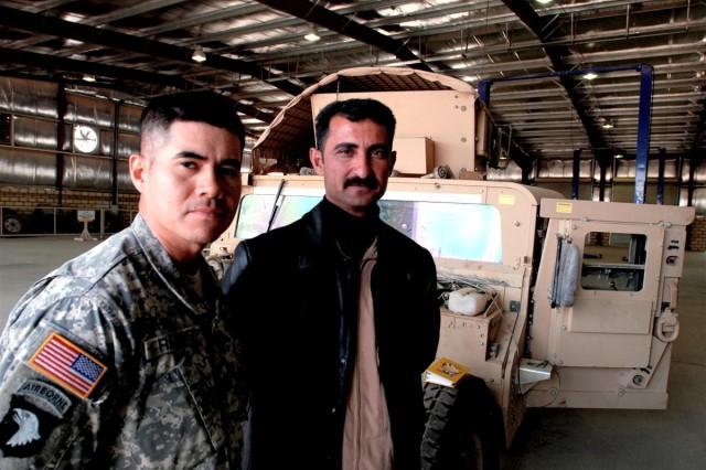 Staff Sgt. Gualberto M. Ramos, 584th Maintenance Co., 101st Airborne Div., with Iraqi mechanic Rafeh Jameel Mekhlef at the Al Asad medium workshop, Camp Mejid, Iraq, Feb. 19. Ramos is part of a Logistics Training and Advisory Team who are partnered with the Iraqi Army to train and mentor mechanics at the facility.