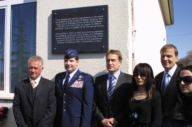 Croatian and American dignitaries including the U.S. Ambassador to Croatia pose in front of a plaque outside a newly renovated  playground in Debeljak, Croatia, dedicated to the memory of native son and U.S. Soldier killed in Iraq in 2005, Master Sgt. Ivica Jerak.