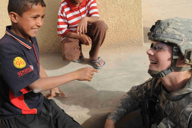 A local Iraqi boy shares a laugh with Spc. Nicole Willson, of Hillsdale, Mich., during a site assessment mission April 18 in the Al-Madain area of eastern Baghdad. Willson, a combat medic assigned to the Brigade Special Troops Battalion, 3rd Brigade Combat Team, 82nd Airborne Division, Multi-National Division - Baghdad, along with her fellow Paratroopers were assessing soccer fields in the area in preparation for a series of soccer clinics and tournaments which will be organized by FC Unity.  Paratroopers also distributed several soccer balls donated by the Kick for Nick organization. The organization honors the memory of a fallen U.S. Soldier, Pfc. Nick Madaras, whose wish was to share his love of soccer with the children of Iraq. Madaras was killed by an improvised explosive device while conducting combat operations Sept. 3, 2006.