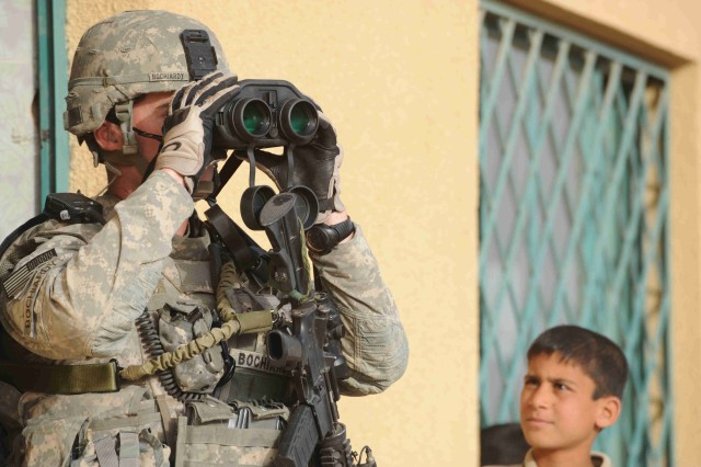 BAGHDAD - Sgt. Matt Bochiardy, of New Smyrna Beach, Fla., uses binoculars to scan the area for threats while providing security during a visit to a soccer field during a site assessment mission April 18 in the al-Madain area of eastern Baghdad. Bochiardy, assigned to the Headquarters and Headquarters Company, 3rd Brigade Combat Team, 82nd Airborne Division, Multi-National Division-Baghdad, and Paratroopers assessed soccer fields in the area before a series of soccer clinics and tournaments organized by FC Unity. The London-based organization promotes the development of unity through soccer-based programs. The clinic is scheduled to take place in mid-May.