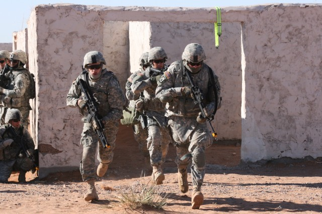 Guardsmen from C Company, 2nd Battalion, 127th Infantry Regiment, dash out of a building in pursuit of high-value targets during urban-operations training at McGregor Range, N.M.