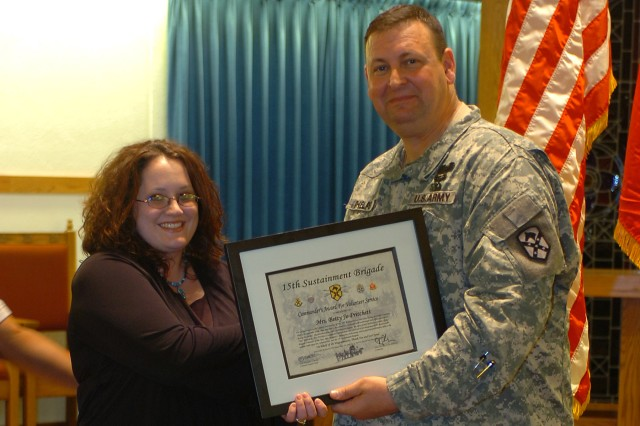 Col. Larry Phelps, the commander of the 15th Sustainment Brigade, 13th Sustainment Command (Expeditionary), presents the volunteer of the year award to Betty Jo Pritchett, a volunteer from the 49th Transportation Battalion for her efforts over the past year.