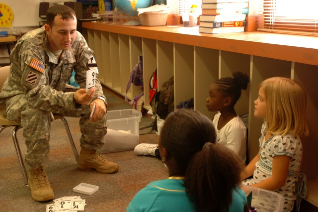 Staff Sgt. Ryan Welch, 3rd Brigade Special Troops Battalion, 3rd Heavy Brigade Combat Team, 1st Cavalry Division, Rear Detachment, of Charlottesville, Va., quizzes second-graders Keirra Capers, 8 (foreground),  Erin Signs, 7, and Galysia Simon, 8, April 20, through the battalion's Adopt-A-School program at Maxdale Elementary School in Killeen, Texas.