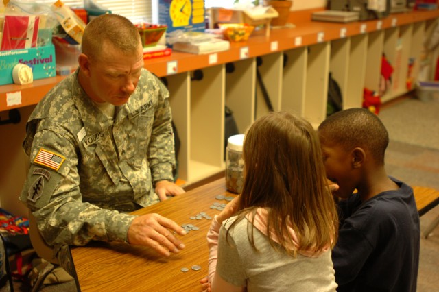 Sgt. Brad Wood, 3rd Brigade Special Troops Battalion, 3rd Heavy Brigade Combat Team, 1st Cavalry Division, Rear Detachment, from Roxton, Texas, practices counting coins with second-graders Hannah Shoopman, 8, and Marshane Haynes, 8, April 20, through the battalion's Adopt-A-School program at Maxdale Elementary School in Killeen, Texas.