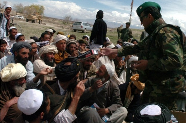Afghan National Army Lt. Col. Attauallah, commander of the 1st Company, 1st Kandak, 203rd Corps of the ANA, hands out radios to elders of the Kalagu area in the Zormat District, Paktya province following a Shura held April 13, to discuss the establishment of Combat Outpost Kalagu.