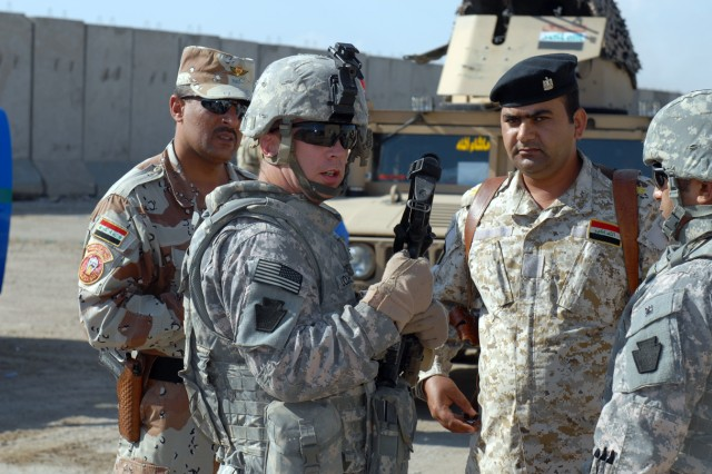 BAGHDAD - Sgt.1st Class, Timothy Lochel, a native of Philadelphia, who is a platoon sergeant, assigned to B Troop, 2nd Squadron, 104th Cavalry Regiment, 56th Stryker Brigade Combat Team meets with members of the 3rd Battalion, 22nd Brigade, 6th Iraqi Army Division to plan a patrol in streets of Sab al-Bour, April 14.  The Iraqi Security Forces of Sab al-Bour patrol the streets daily with the assistance of B Troop.