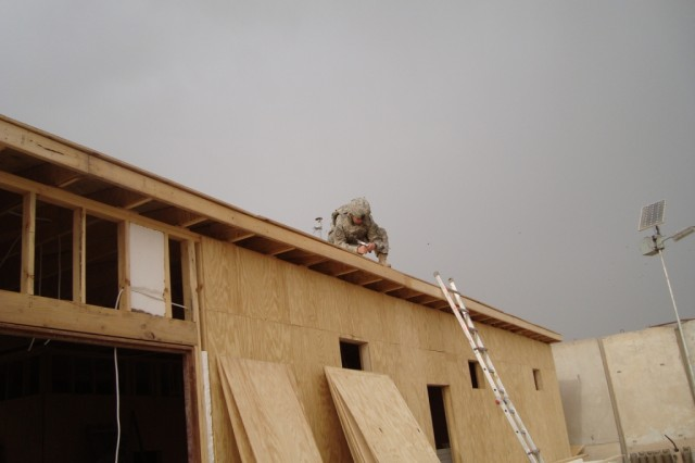 BAGHDAD - Pvt. Benjamin Livsey, carpenter, 46th Engineer Combat Battalion (Heavy), 225th Engineer Brigade, from Stillwater, Okla., nails tin to the roof of the new battalion aid station March 28 on Joint Security Station Ur.