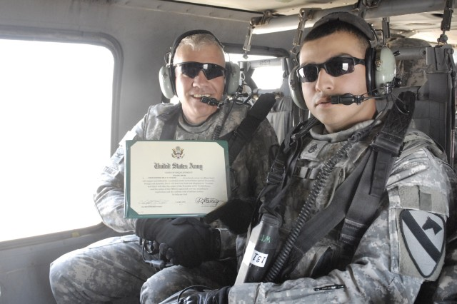 Col. Philip Battaglia, Commander of the 4th Brigade Combat Team, 1st Cavalry Division, re-enlists Staff Sgt. Christopher Toledo, assigned to the 4th Brigade Special Troops Battalion, 4th Brigade Combat Team, 1st Cavalry Division, in a UH-60 Black Hawk Helicopter above Contingency Operating Base Adder, Iraq, recently.