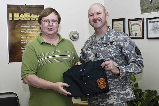 Fort Riley Garrison Command Sgt. Maj. Ian Mann presents a shirt to Floyd Hansford, a visual information specialist at DOIM. The shirt features a new garrison IMCOM logo Hansford designed.
