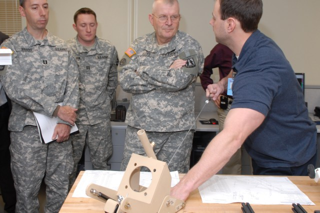 Maj. Gen. Dennis E. Lutz, commander of the 335th Signal Command, watches as Tim Knabel demonstrates how the antenna flex-mount operates.  Employees here are fabricating and assembling the device, which allows the antenna to tilt down prior to coming into contact with a hard object such as an overpass, bridge or low-hanging wires. Knabel is a mechanical engineer in the Production Engineering Directorate.  During his April 2 visit Lutz was briefed on depot operations and Lean Six Sigma.  He also toured the High Tech Regional Training Site and met with members of the Bravo Company, 392 Signal Battalion.""