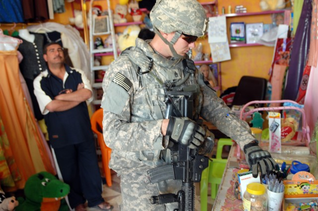 Anadarko, Okla. native Staff Sgt. Tim Winn, a section sergeant and cavalry scout from assigned to Apache Troop, 1st Squadron, 7th Cavalry Regiment, checks out a local vendor's merchandise in Thalba, April 13.