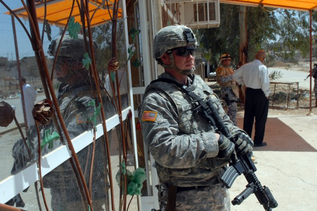 Staff Sgt. Daniel McHenry, a cavalry scout squad leader from Zanesville, Ohio, assigned to Apache Troop, 1st Squadron, 7th Cavalry Regiment, stands guard outside of a shop while his platoon leader discusses a possible micro-grant with the business owner here, April 13.
