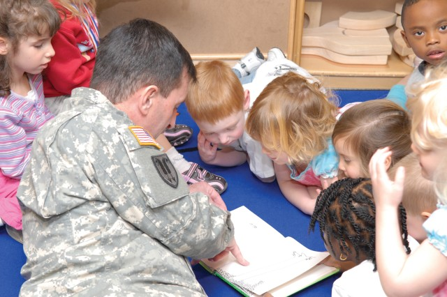 "Depot commander, Col. Ron Alberto reads Shel Silverstein's ""The Giving Tree"" to a group of 3- and 4-year-old children April 14.  The depot's Child, Youth and School Services Program will host numerous events this month to celebrate the Month of the Military Child.  """