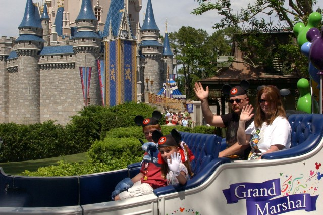 "Sgt. James Hill and his wife, Keri, their son Austin, 11 and daughter Jessy, 8,  from Canton, N.C., wave to the tens of thousands of cheering onlookers during Disney World's ""Celebrate a Dream Come True"" parade. Together with their son, Austin, and daughter, Jessy, the Hill family was selected by the Army Reserve Yellow Ribbon staff to be honored by Disney in recognition of the Month of the Military Child as the Grand Marshal of the parade. The Hills were attending the the Yellow Ribbon Reintegration Workshop held in Orlando April 17-19. Sponsored by 81st Regional Support Command, the workshop brought nearly 700 Soldiers and their families for the three-day event to assist them with the tools to succeed after a deployment. Soldiers are given timely information about available services and referrals, and provide a proactive outreach to help overcome the stresses of deployment."""