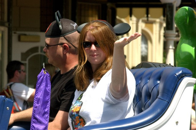 "Sgt. James Hill and his wife, Keri, from Canton, N.C., wave to tens of thousands of cheering onlookers during Disney World's ""Celebrate a Dream Come True"" parade. Together with their son, Austin, and daughter, Jessy, the Hill family was selected by the Army Reserve Yellow Ribbon staff to be honored by Disney in recognition of the Month of the Military Child as the Grand Marshal of the parade. The Hills were attending the the Yellow Ribbon Reintegration Workshop held in Orlando April 17-19. Sponsored by 81st Regional Support Command, the workshop brought nearly 700 Soldiers and their families for the three-day event to assist them with the tools to succeed after a deployment. Soldiers are given timely information about available services and referrals, and provide a proactive outreach to help overcome the stresses of deployment."""
