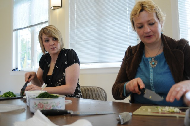 """Air Force Staff Sgt. Reychal Davis, a Defense Threat Reduction Agency student, and Elena Shulgina, a DTRA teacher, cut vegetables for their feast or """"banket"""" (in Russian)."""