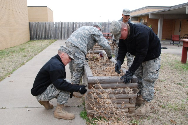 Soldiers from the 541st Combat Sustainment Support Battalion, 1st Sustainment Brigade, clear debris from a flower bed April 2 at the Kansas Veterans Home in Winfield.