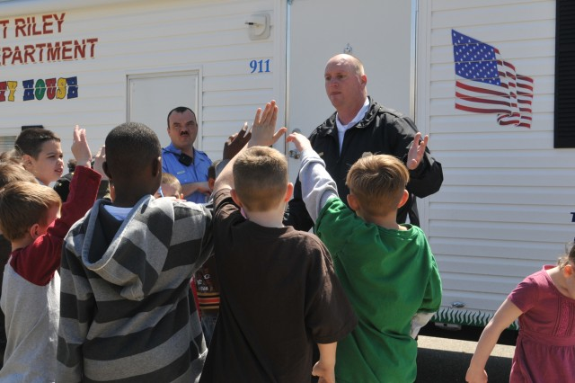 Shawn Sullivan questions kids about what to do in the event of a fire in their homes before they enter Fort Riley's fire safety trailer April 10.