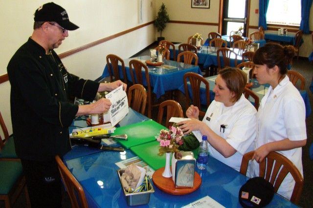 Pvt. Jessica Fleming, (seated) and Sgt. Ahra Barrera, Soldier culinarians with 501st Military Intelligence Brigade take notes on how to carve an outline of an M1 Abrams tank into a watermelon during culinary display training with 2008 Food Network Challenge Fantasy Fruit Sculpture Gold Medalist Chef Ray Duey during his visit to the Humphreys Garrison Red Dragon DFAC April 20 - May 2.