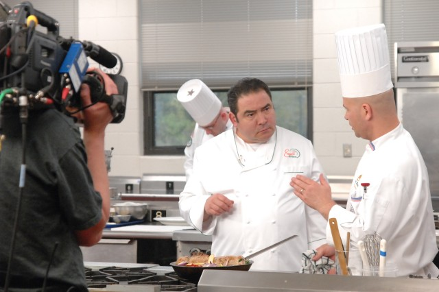 Chef Emeril Lagasse talks with Staff Sgt. David Baisden, food service instructor at the Army Center of Excellence, Subsistence, in between takes April 18. Emeril visited Fort Lee, Va., to film two segments of his new Discovery Channel show. Photo by Mike Strasser, Fort Lee Public Affairs.