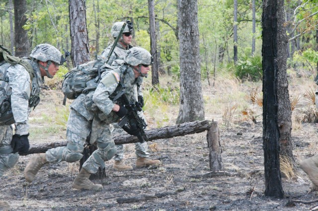 Soldiers of A Co., 1/30 Inf., rush forward from their canceled position. The soldiers bobbed and weaved through the trees as they advanced through the woods towards their objective, a small wooden house.  The maneuver was part of a Bradley Table 12 exercise being conducted at Fort Stewart, April 20. ""