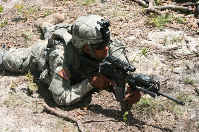 Private Alexander Rosario, A Co., 1/30 Inf., takes a prone position to provide support by fire to fellow Soldiers during a Bradley Table 12 exercise. Private Rosario was part of two teams bounding through the woods to take an objective at the edge of the tree line during field exercises at Fort Stewart, April 20.