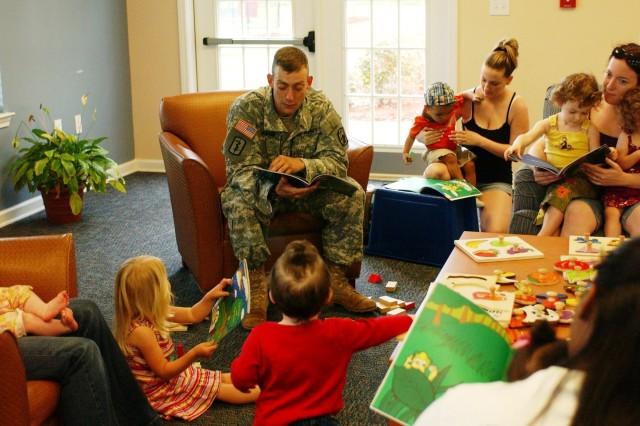 """Staff Sergeant James Menard, 473rd QM Co., 260th QM Bn., reads """"The Bees and the Bears"""" to a room of about 20 children, ages 2-5, and their parents at """"Story Time"""" at the New Gannam Housing area on Hunter Army Airfield, Ga., April 14. Staff Sergeant Menard wrote the book about three years ago to help his son, who was then 2-years-old, understand his deployment to Iraq. Book illustrations were done by his brother, John Menard."""