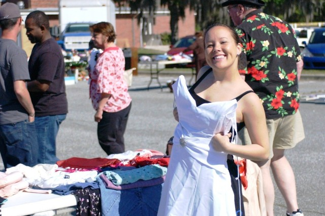 Specialist Monica Smith, HHC, CAB, a vendor and a shopper at the MWR Yard Sale, is delighted to buy a formal gown from an adjacent booth for $35.