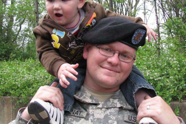 Nineteen-month-old Jacob Galinat sits on the shoulders of his dad, Reserve Spc. Mark Galinat of Murfreesboro, Tenn., following the 375thAca,!a,,cs deployment ceremony.