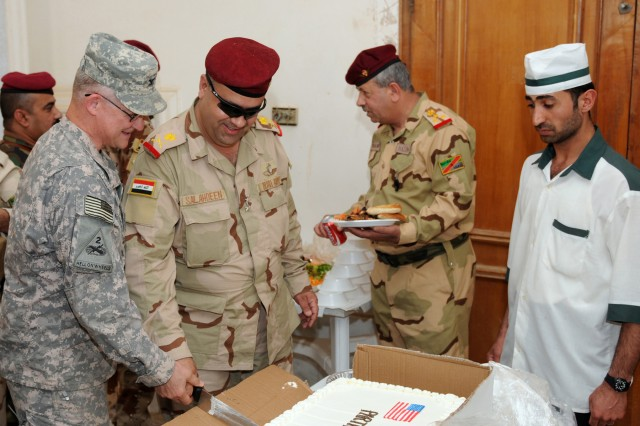 CONTINGENCY OPERATING BASE SPEICHER, TIKRIT, Iraq - Col. Gary David, commander of 4th Iraqi Army Division military transition team, and Gen. Salah, 4th IA Div. command, cut a cake together to commemorate Iraqi and Coalition Force's 1st Partnership Day at Forward Operating Base Dagger, April 9.