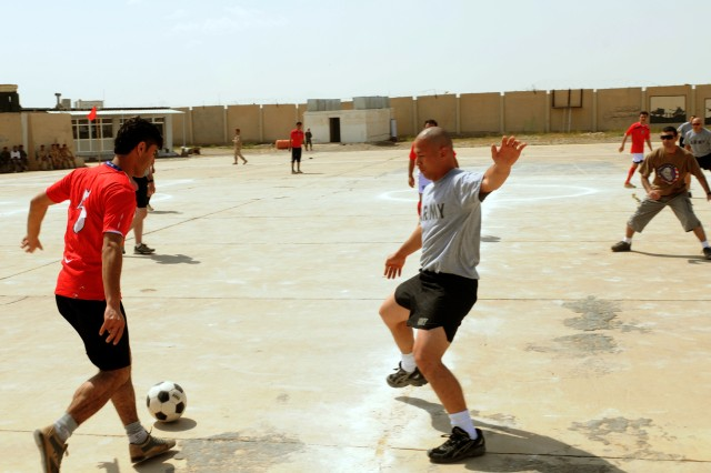 CONTINGENCY OPERATING BASE SPEICHER, TIKRIT, Iraq - A member of the Iraqi Army soccer team attempts to make his move past Capt. Jerrold Castro, communications officer, 4th IA Div MiTT during the competitive sports phase of Coalition and Iraqi Force's 1st Partnership Day at Forward Operating Base Dagger, April 9.